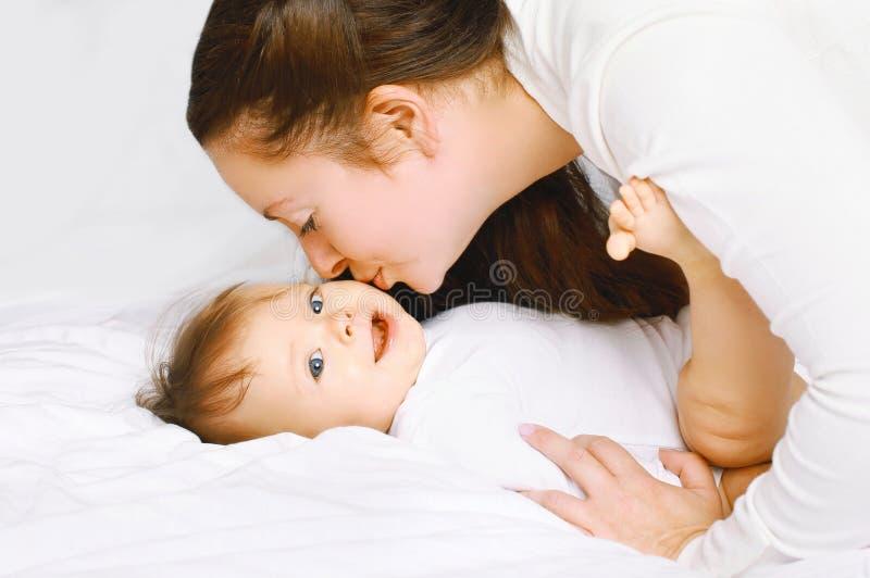 Madre che bacia bambino sveglio sul letto immagini stock