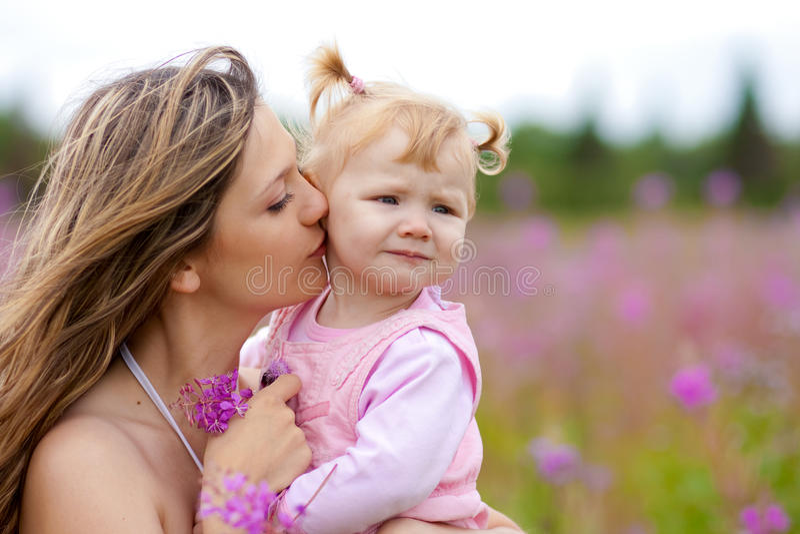 Madre che bacia figlia in prato esterno fotografia stock