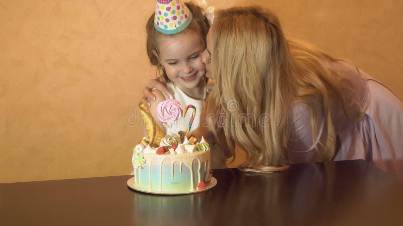 Madre che bacia figlia sulla festa di compleanno torta di compleanno sulla tavola fotografia stock libera da diritti