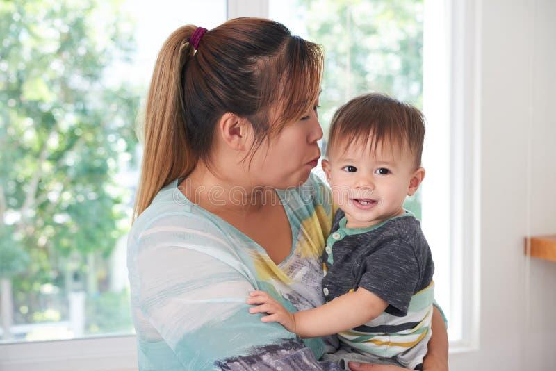 Madre che bacia figlio fotografia stock