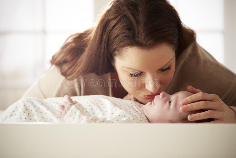 Madre che bacia neonato che si trova sulla Tabella cambiante in scuola materna immagini stock libere da diritti