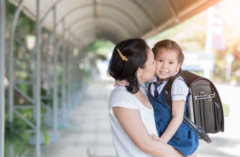 Madre che bacia scolara in uniforme fotografie stock