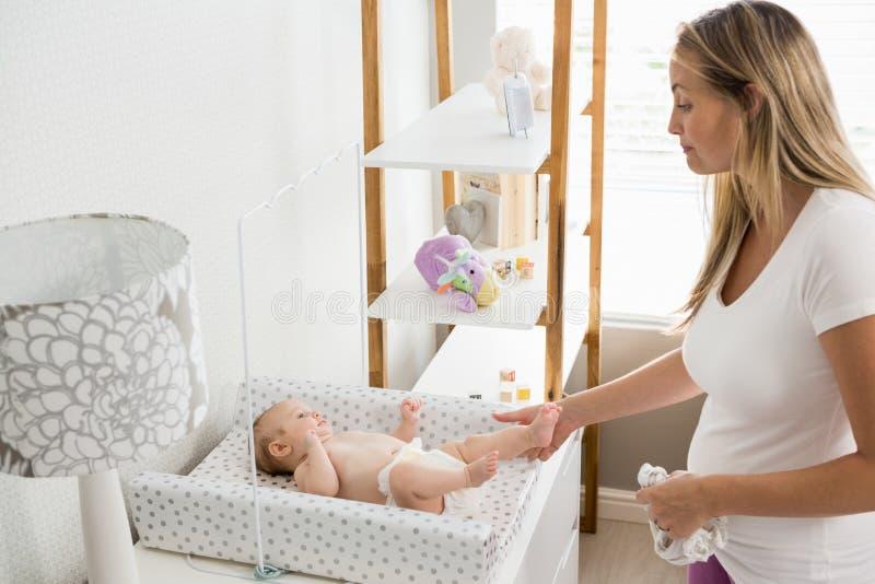 Madre che cambia il pannolino del suo bambino fotografia stock libera da diritti