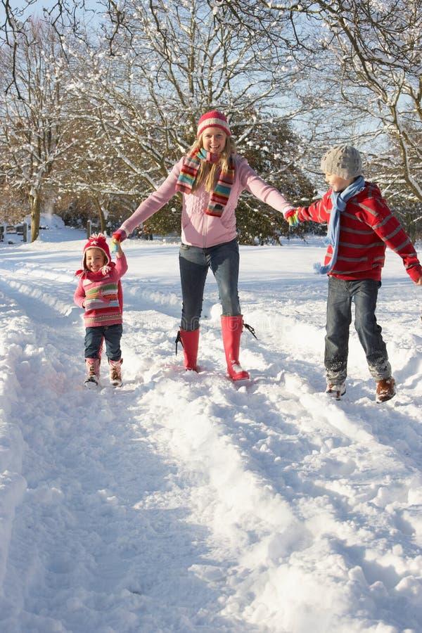 Madre che cammina con i bambini attraverso Snowy Landsca fotografie stock