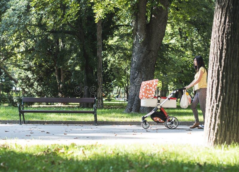 Madre che cammina nel parco con la carrozzina fotografie stock