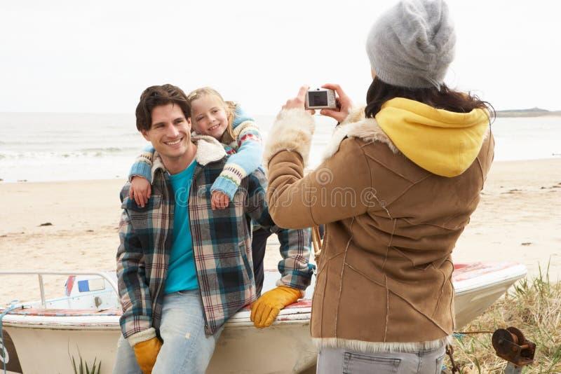 Madre che cattura la fotografia della famiglia sulla spiaggia di inverno fotografia stock libera da diritti