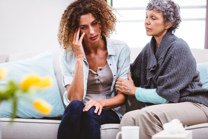 Madre che conforta figlia triste che si siede sul sofà immagini stock libere da diritti