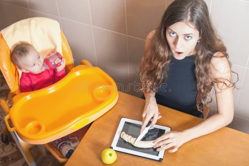 Madre che cucina alimenti per bambini alla compressa del pc immagine stock libera da diritti