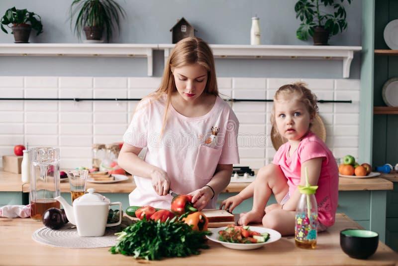 Madre che cucina cena sulla cucina con il suo piccolo bambino sveglio fotografia stock