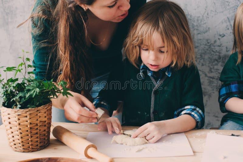 Madre che cucina con i bambini in cucina Fratelli germani del bambino che cuociono insieme e che giocano con la pasticceria a cas immagine stock libera da diritti
