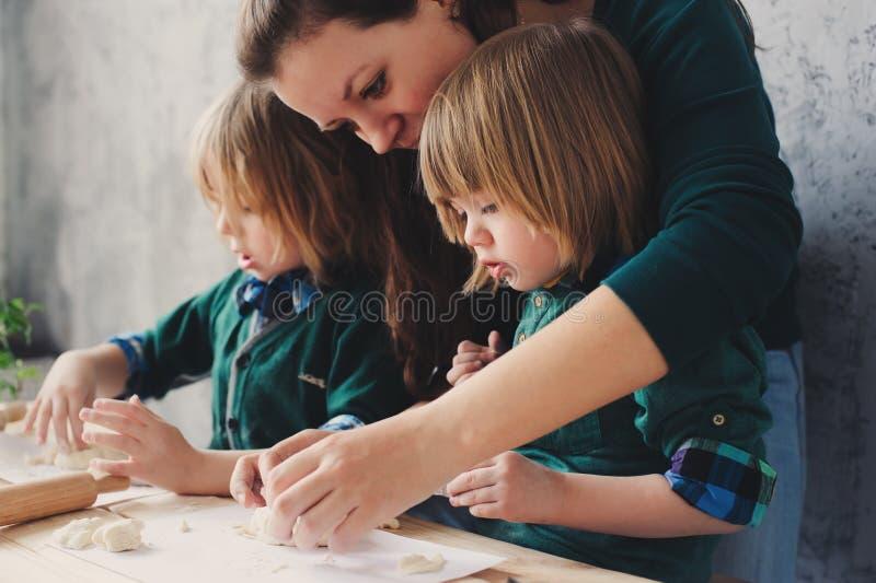 Madre che cucina con i bambini in cucina Fratelli germani del bambino che cuociono insieme e che giocano con la pasticceria a cas immagini stock