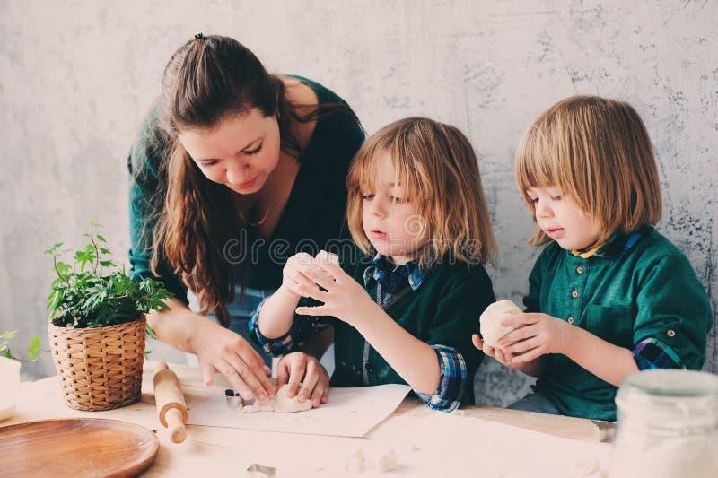 Madre che cucina con i bambini in cucina Fratelli germani del bambino che cuociono insieme e che giocano con la pasticceria a cas fotografie stock libere da diritti