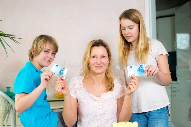 Madre che dà ai suoi bambini denaro per piccole spese fotografia stock libera da diritti