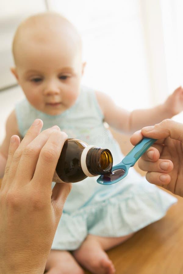 Madre che dà la medicina del bambino all'interno fotografia stock