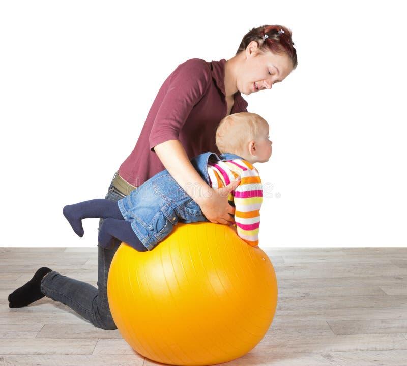 Madre che esercita il suo giovane bambino immagine stock