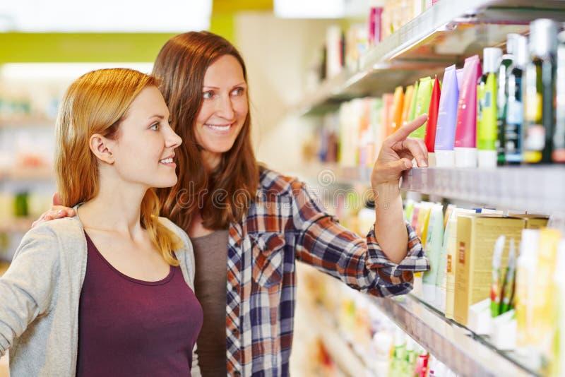 Madre che esprime parere di acquisto della figlia in farmacia fotografie stock libere da diritti