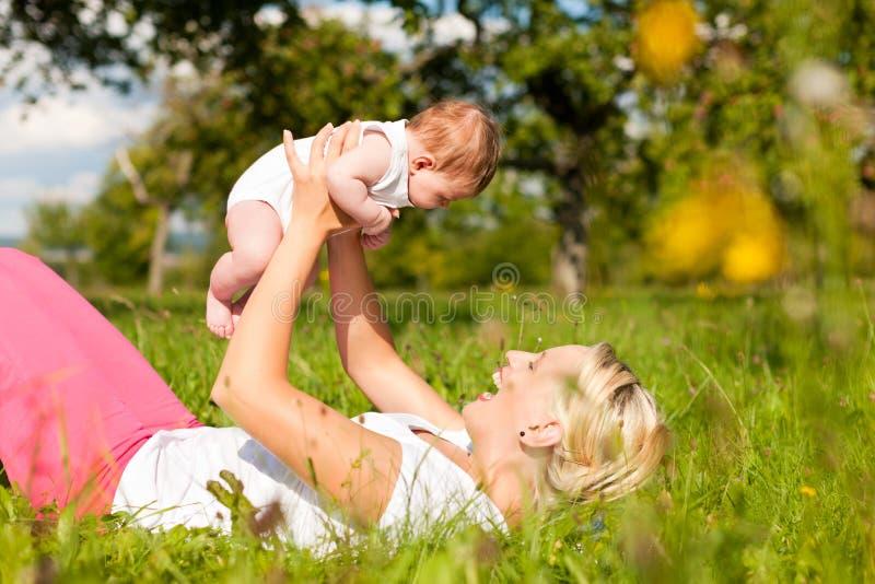 Madre che gioca con il bambino sul prato immagini stock libere da diritti