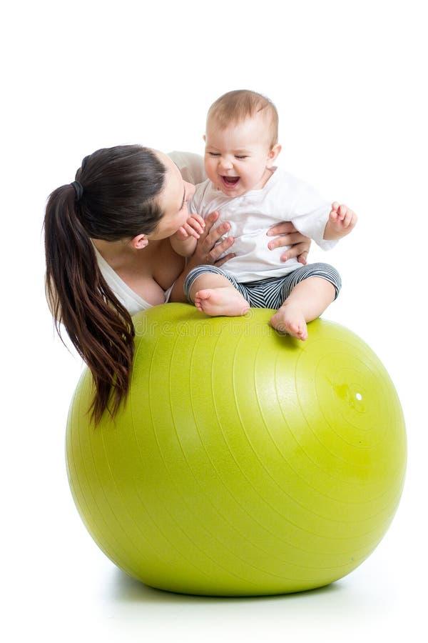 Madre che gioca con il bambino sulla palla di misura immagini stock