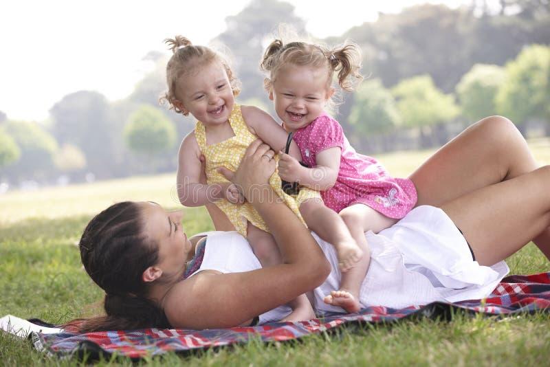 Madre che gioca con le figlie fotografia stock