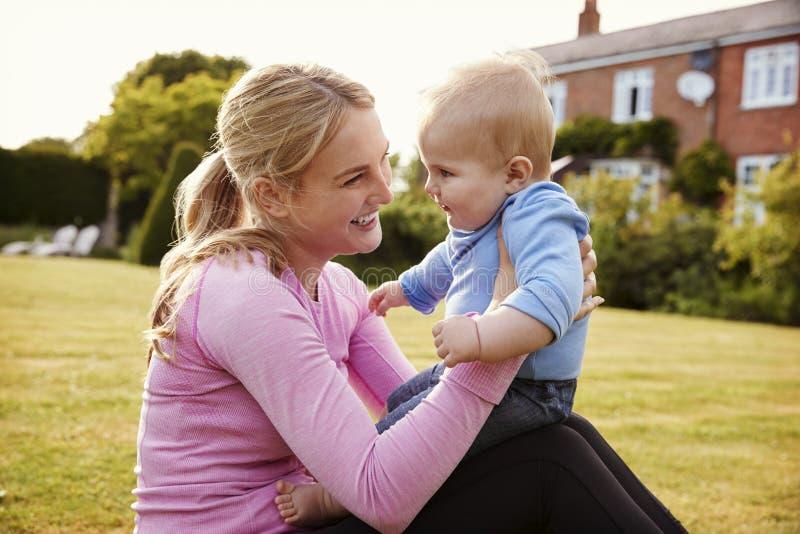 Madre che gioca nel giardino con il figlio del bambino immagine stock