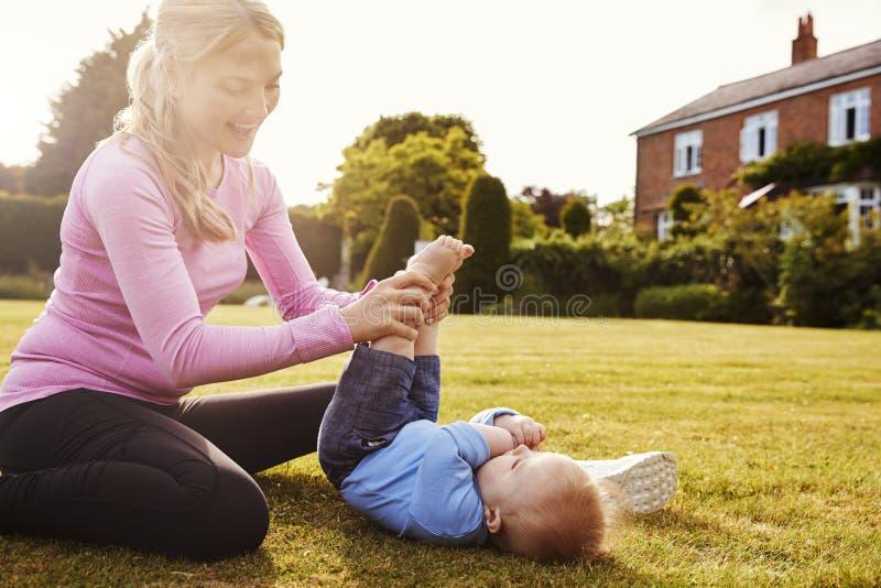 Madre che gioca nel giardino con il figlio del bambino fotografia stock