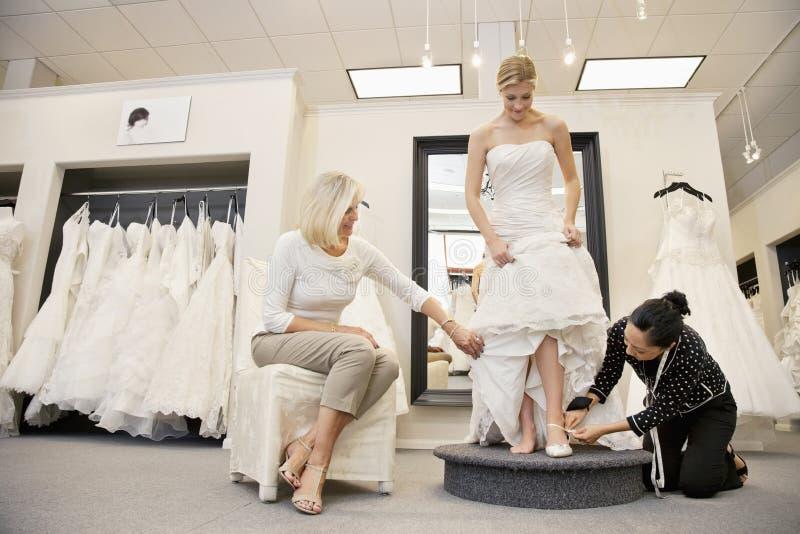 Madre che guarda come sposa d'aiuto degli impiegati maturi con calzature in boutique nuziale fotografie stock libere da diritti