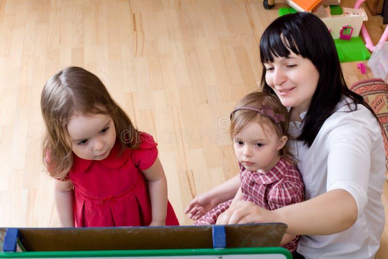 Madre che insegna alle sue figlie fotografie stock libere da diritti