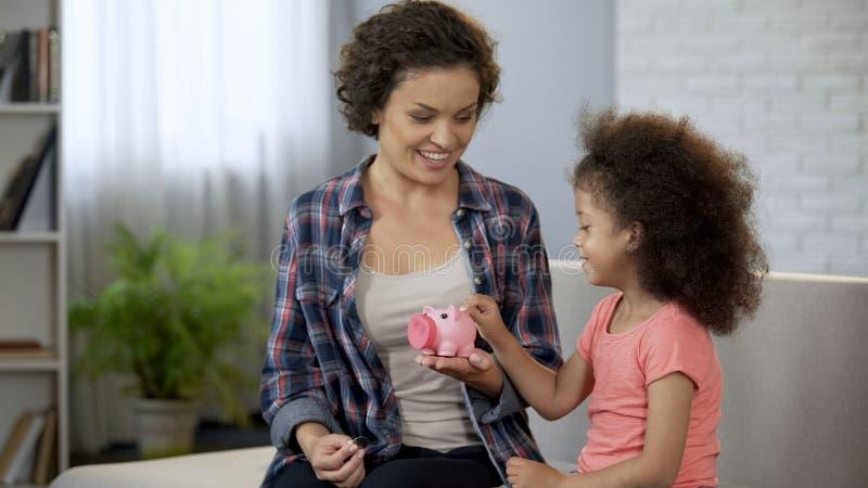 Madre che insegna a poca figlia a risparmiare soldi, monete di lancio in porcellino salvadanaio immagini stock