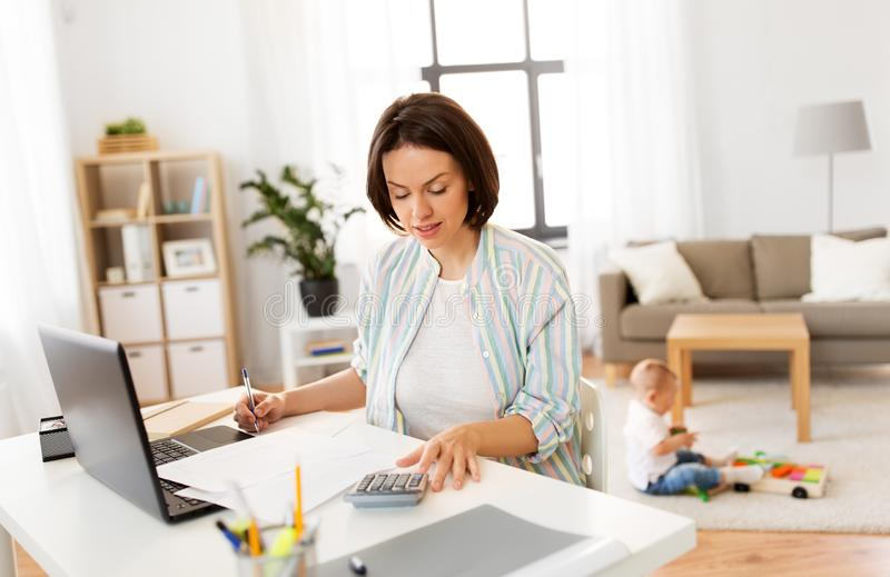 Madre che lavora al computer portatile ed al neonato a casa fotografia stock