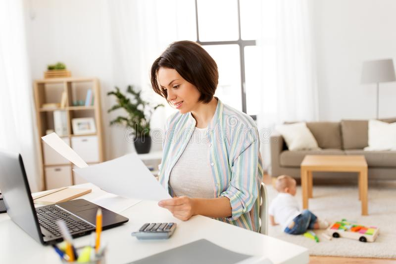 Madre che lavora con le carte ed il neonato a casa fotografia stock libera da diritti
