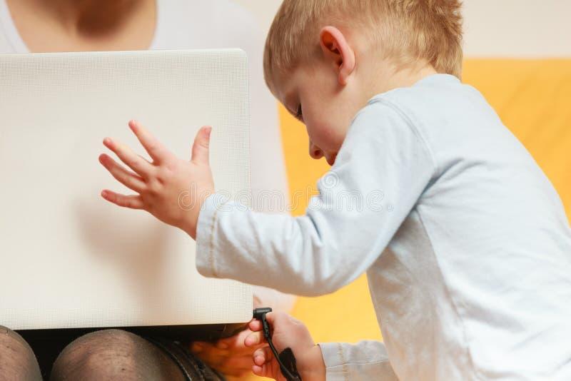 Madre che lavora facendo uso del computer portatile, disturbo del ragazzino fotografie stock