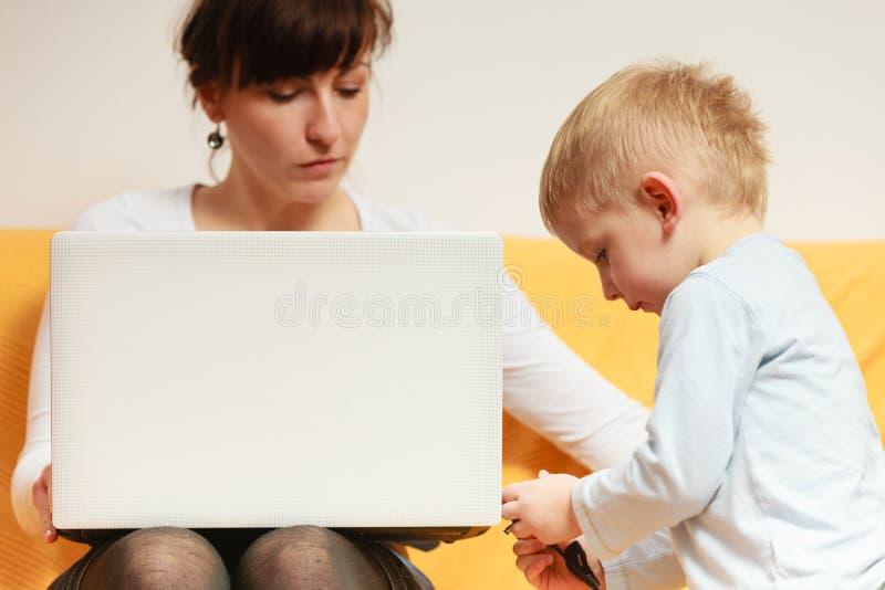 Madre che lavora facendo uso del computer portatile, disturbo del ragazzino immagini stock