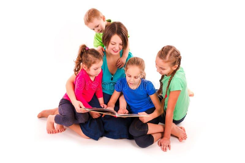 Madre che legge un libro ai bambini fotografia stock libera da diritti