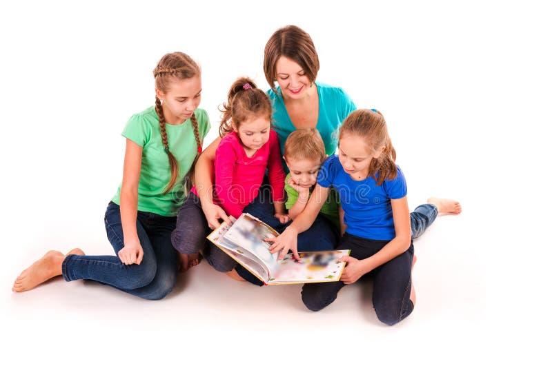 Madre che legge un libro ai bambini immagini stock libere da diritti