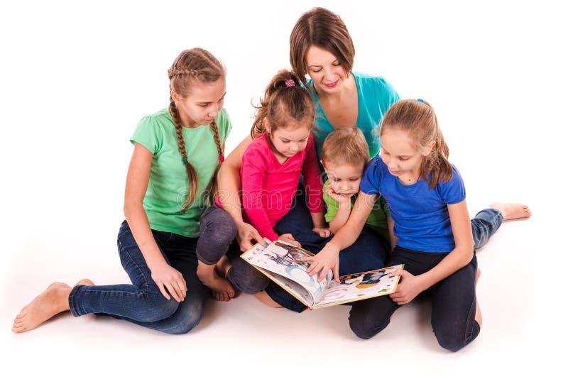 Madre che legge un libro ai bambini isolati fotografia stock libera da diritti