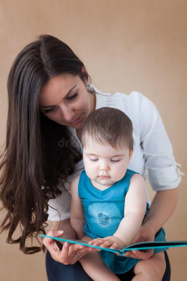Madre che legge un libro alla sua neonata fotografie stock libere da diritti