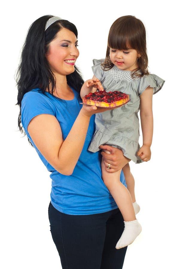 Madre che offre frutta acida alla sua figlia fotografia stock