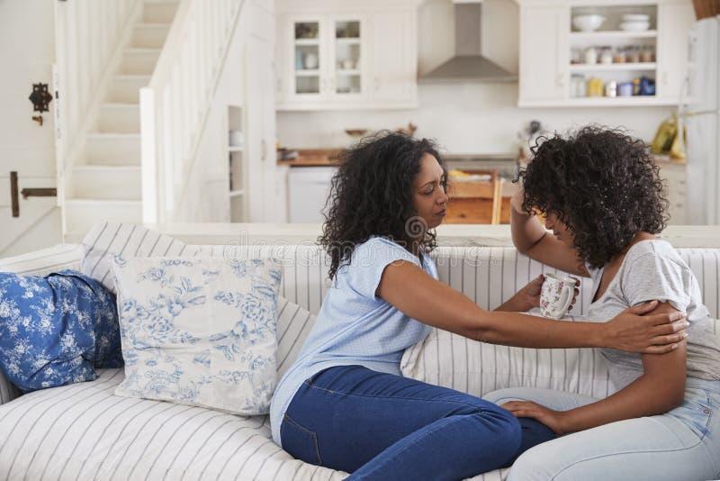 Madre che parla con la figlia adolescente infelice sul sofà immagine stock libera da diritti