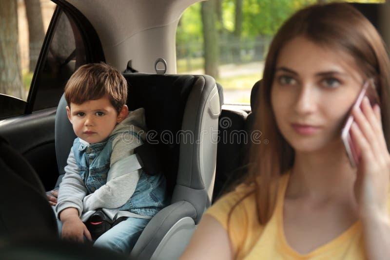 Madre che parla dal telefono mentre conducendo automobile con suo figlio sul sedile posteriore BAMBINO IN PERICOLO immagine stock