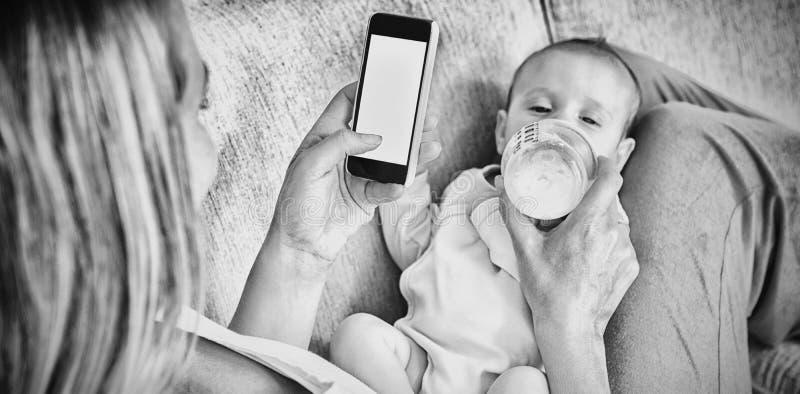 Madre che per mezzo del telefono cellulare mentre alimentando il suo bambino con la bottiglia per il latte immagini stock