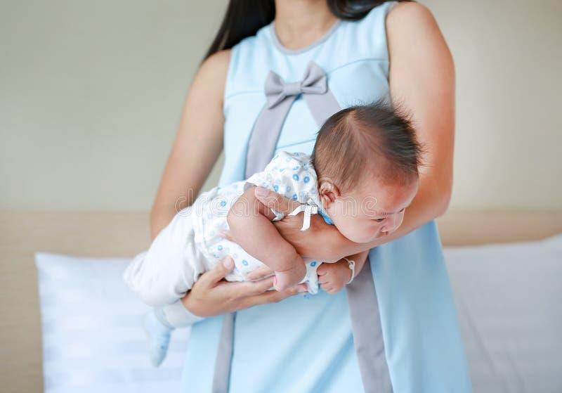 Madre che porta in alto il bambino piccolo per diminuire il dolore allo stomaco Concetto di igiene per i bambini fotografia stock