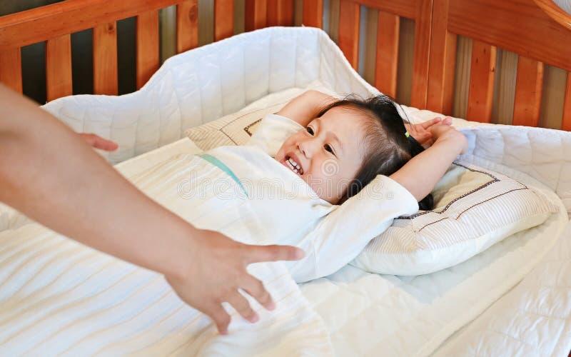 Madre che prende figlia per dormire sul letto ad ora di andare a letto fotografia stock