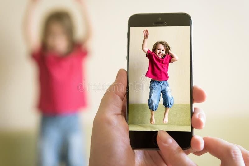 Madre che prende foto della neonata di salto con il suo telefono cellulare fotografia stock libera da diritti