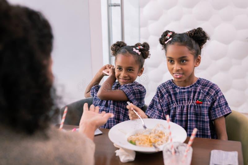 Madre che prende smartphone a partire dalla sua piccola figlia mentre pranzando fotografie stock libere da diritti