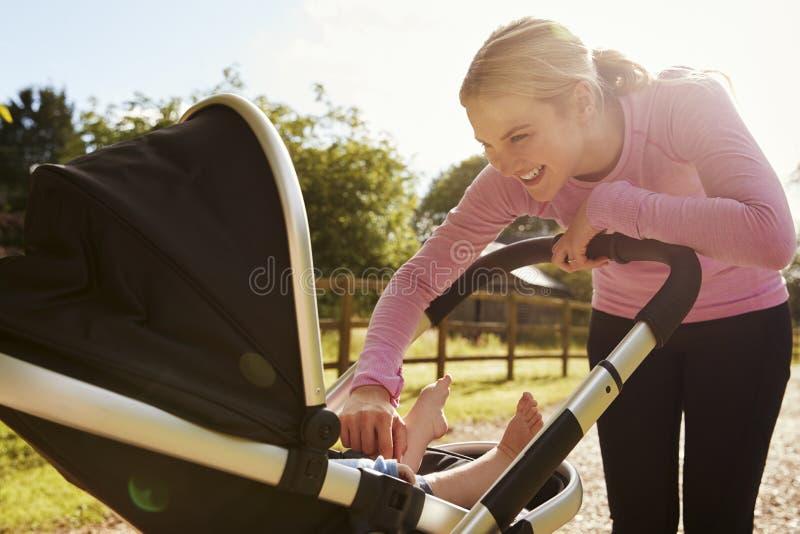 Madre che si esercita correndo mentre spingendo carrozzina immagine stock libera da diritti