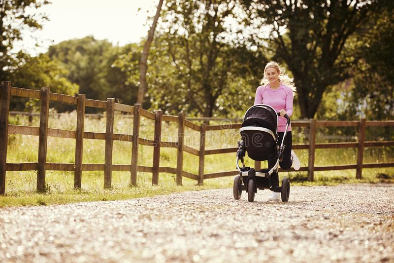 Madre che si esercita correndo mentre spingendo carrozzina fotografie stock libere da diritti