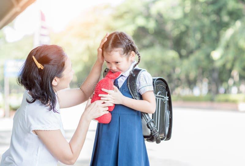 Madre che sta alla scuola che si tiene per mano e che insegna immagine stock