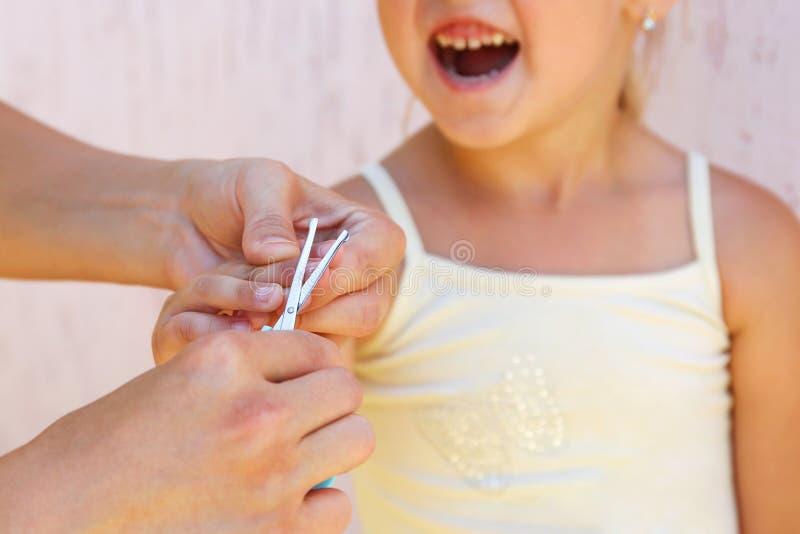 Madre che taglia le sue unghie al bambino fotografia stock libera da diritti