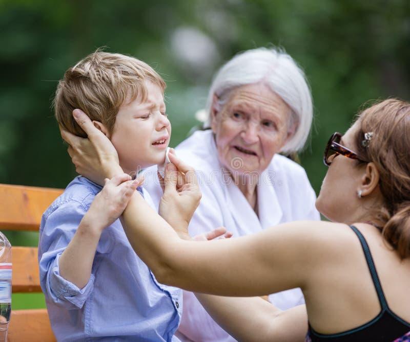 Madre che tratta raschiatura sul mento del ` s del figlio fotografia stock