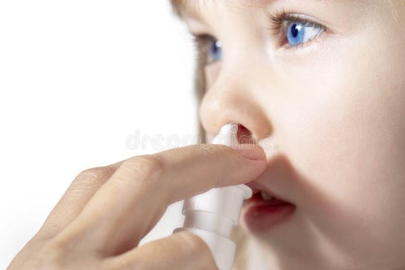 Madre che usando lo spruzzo di naso per curare la sua bambina fotografia stock